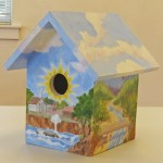 The birdhouse painted by a local artist (artist's name not given).
